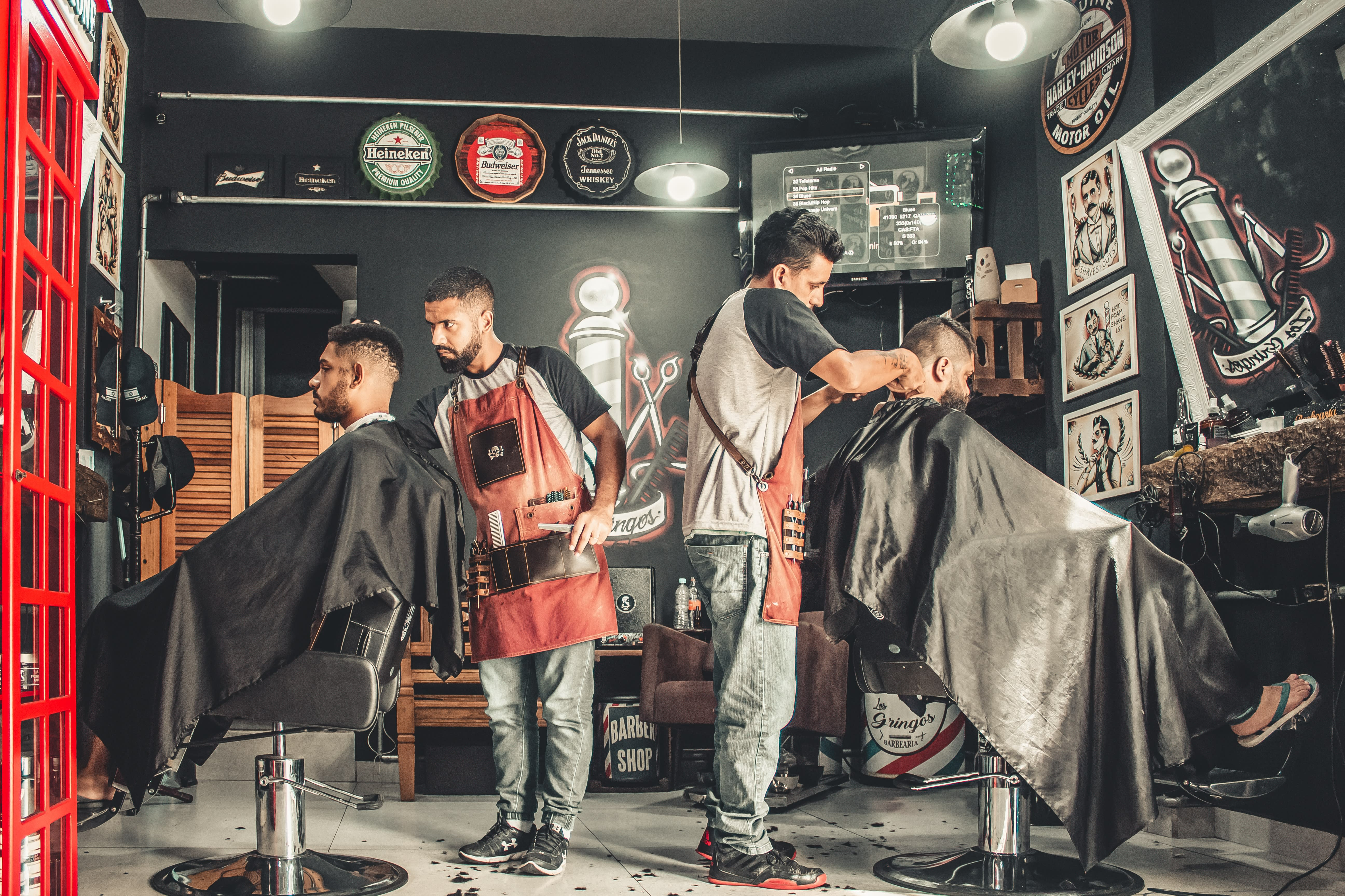 Photo of a barbershop with two barbers at work on their clients