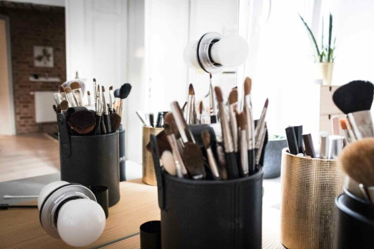 Makeup brushes and other products on a desk at a business, ready to be photographed for Instagram