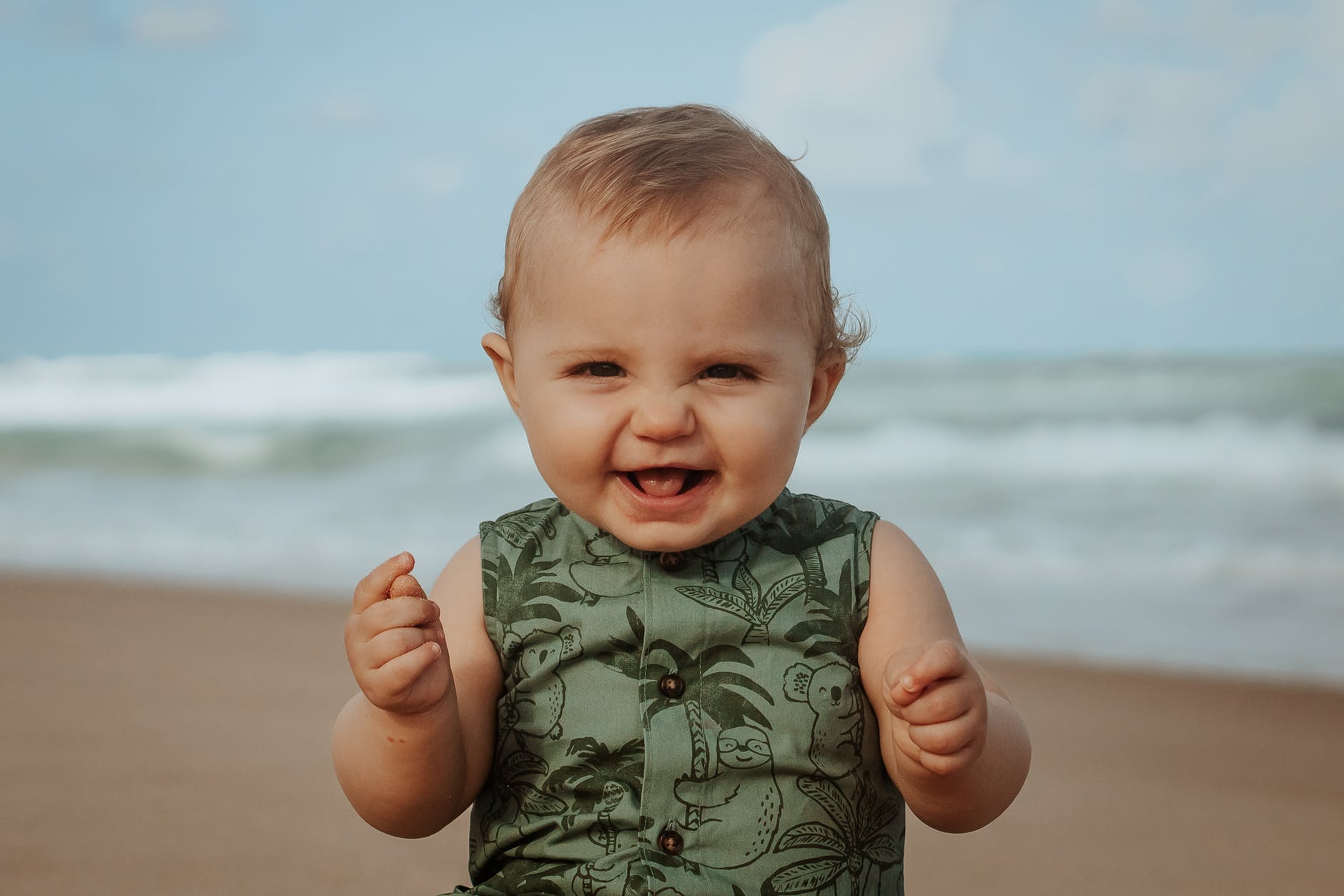 A baby smiling on the beach